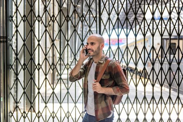 Reisender mann, der über telefon spricht