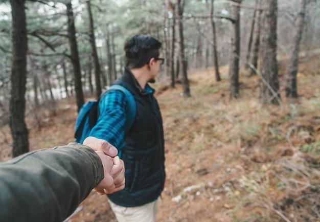 Reisender mann im wald, der hand hält