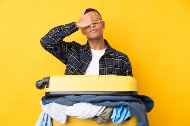 Reisender mann mit einem koffer voller kleidung über isolierten gelben wand, die augen durch hände bedeckt