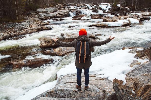 Reisender mann mit einem rucksack, der auf einem felsen steht, die hände auf der seite auf dem bergfluss und dem wasserfall