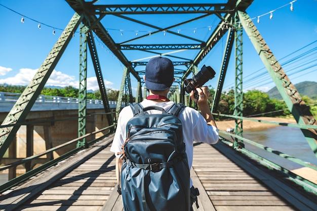 Reisender mann mit kamera auf einer rostigen brücke