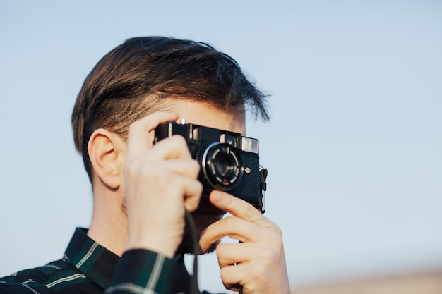 Reisender mann mit retro-kamera