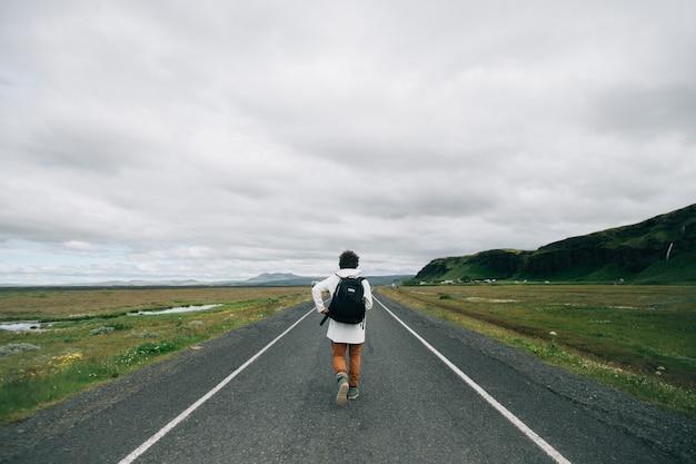 Reisender mann mit rucksack erkunden island