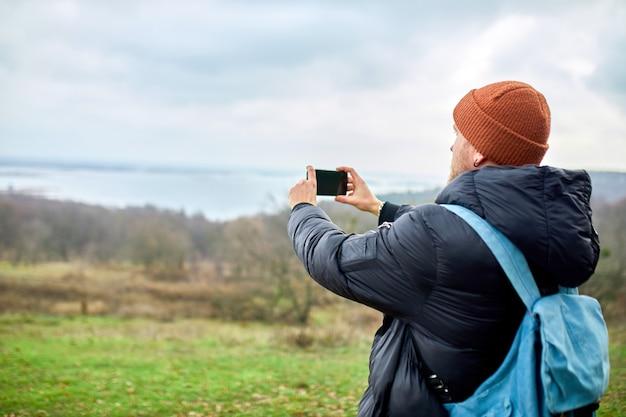 Reisender mann mit rucksack macht fotos oder selfie auf einem smartphone, sein handy mit fluss und bergen lifestyle.
