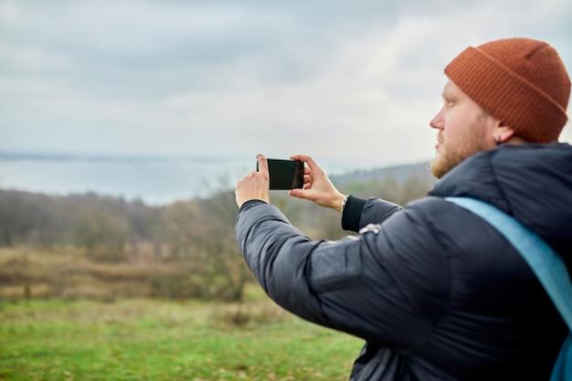 Reisender mann mit rucksack macht fotos oder selfie auf einem smartphone