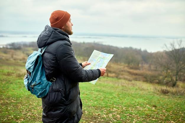 Reisender mann mit rucksack mit karte in der hand auf einer wand des gebirgsflusses der natur, reisekonzept, urlaub und lebensstilwanderkonzept