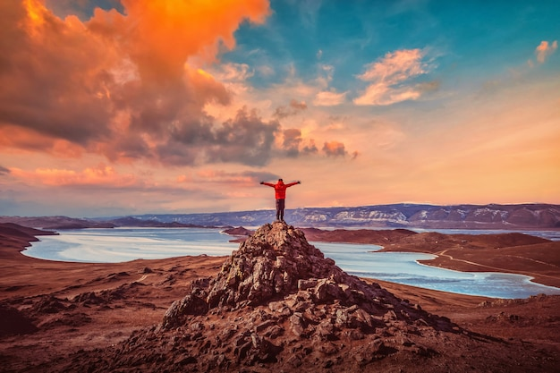 Reisender mann tragen rote kleidung und heben arm, der auf dem gipfel des berges nahe baikalsee, sibirien, russland steht.