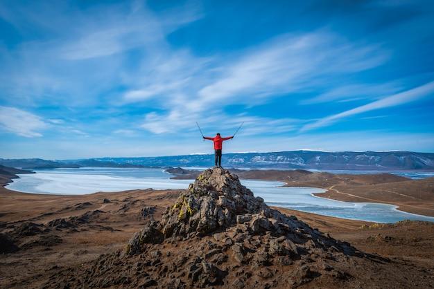 Reisender mann tragen rote kleidung und hebt den arm, der tagsüber auf berg im baikalsee, sibirien, russland steht.