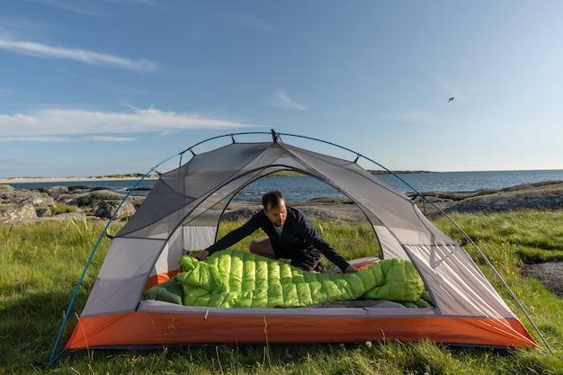 Reisender mann zelt am strand aufstellen
