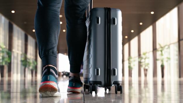 Reisender mit dem koffer, der mit tragendem gepäck und passagier für ausflug im flughafenterminal für flugreisen geht