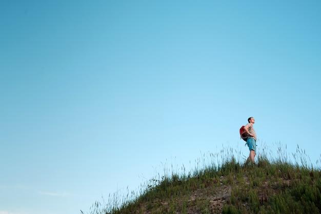 Reisender mit dem orangefarbenen rucksack, der in den hügeln auf blauem himmel wandert