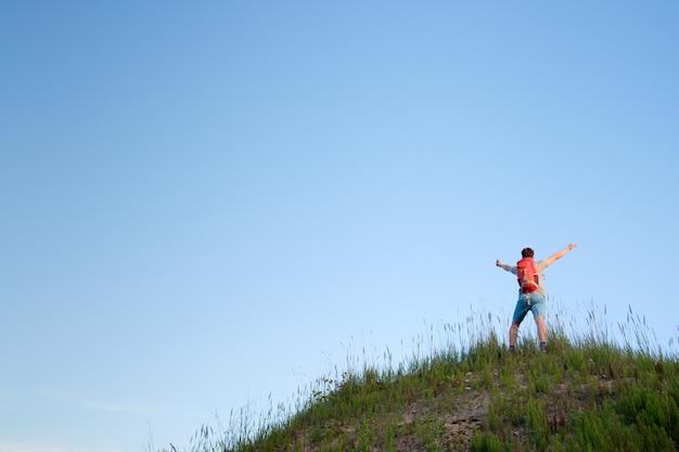 Reisender mit dem orangefarbenen rucksack, der in den hügeln auf blauem himmelhintergrund wandert, ansicht von hinten