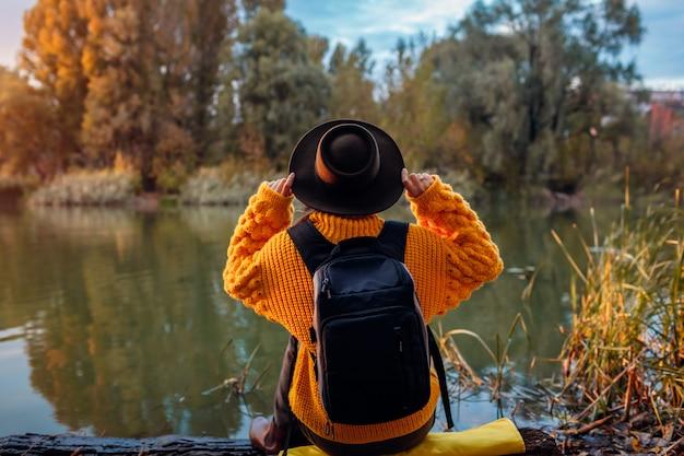 Reisender mit dem rucksack, der durch herbstfluß bei sonnenuntergang sich entspannt. junge frau, die auf bank sitzt und holdinghut sich entspannt