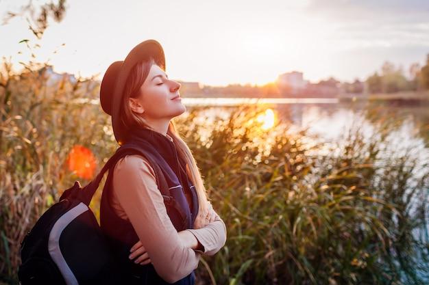 Reisender mit dem rucksack, der durch herbstfluß bei sonnenuntergang sich entspannt. junge frau, die tief atmet, glücklich und frei fühlend
