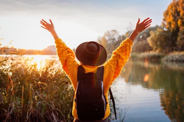 Reisender mit dem rucksack, der durch herbstfluß bei sonnenuntergang sich entspannt. junge frau hob die arme an, die frei und glücklich sich fühlen