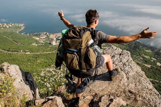 Reisender mit einem touristenrucksack steht auf einem felsigen berg