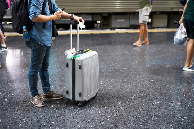 Reisender mit gepäck am bahnhof für reise