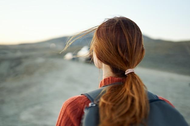 Reisender mit roten haaren und rucksack auf der hintergebirgslandschaftshimmel-rückansicht