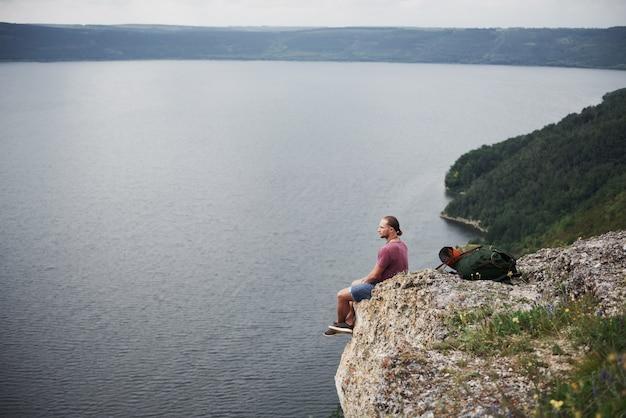 Reisender mit rucksack, der oben auf berg sitzt und blick über der wasseroberfläche genießt. freiheit und aktiver lebensstil konzept