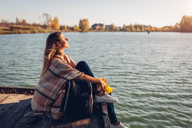 Reisender mit rucksack, der sich bei sonnenuntergang am herbstfluss entspannt. junge frau, die auf pier sitzt, atmen freies gefühl glücklich. aktiver lebensstil