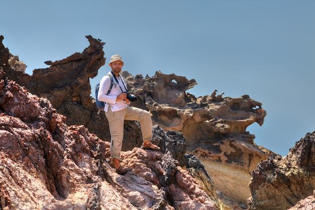 Reisender mit rucksack und kamera steht auf felsen, hormuz island, hormozgan, iran.