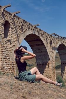 Reisender mit schwarzem hut sitzt im sommer neben der zerstörten alten steinbrücke