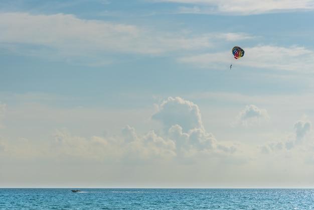 Reisender parasailing mit schnellboot über dem meer