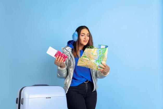 Reisender. porträt der kaukasischen frau auf blauem studiohintergrund. schönes weibliches modell in warmer kleidung. konzept der menschlichen emotionen, gesichtsausdruck, verkauf, anzeige. winterstimmung, weihnachtszeit, feiertage.