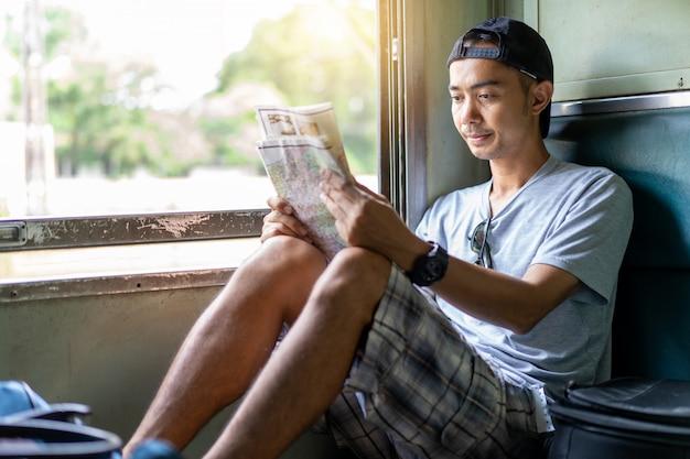 Reisender wanderer des asiatischen mannes, der karte liest, sitzen auf dem alten zugsitz bei thailand