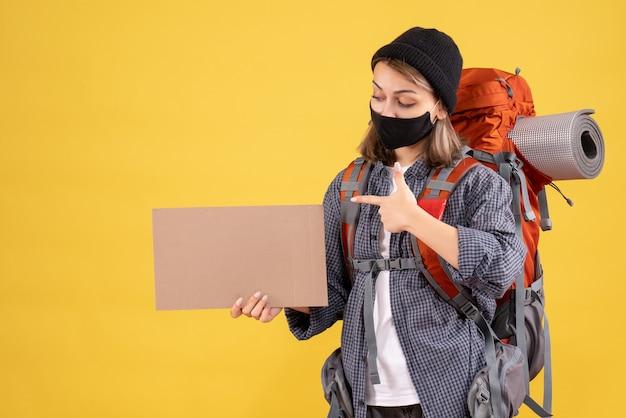 Reisendes mädchen mit schwarzer maske, die auf pappe zeigt