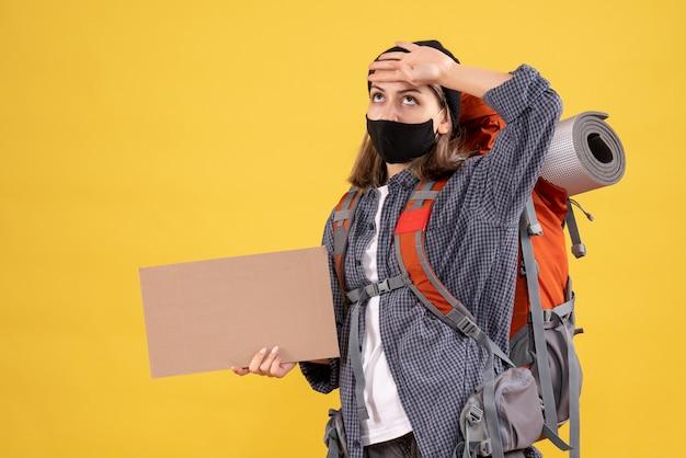 Reisendes mädchen mit schwarzer maske und rucksack, die pappe hält und sich die hand auf den kopf legt