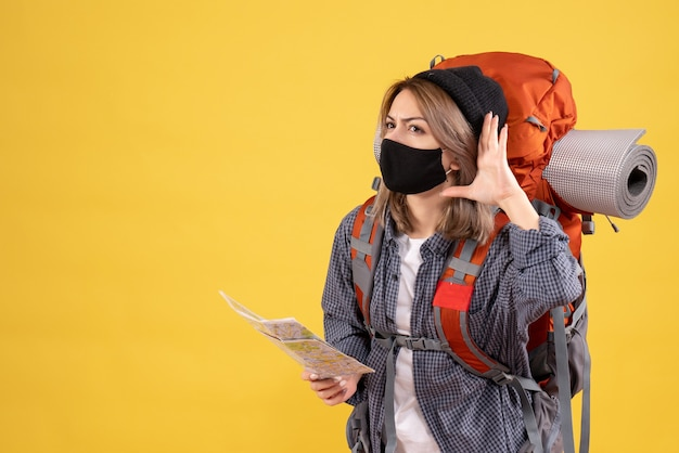 Reisendes mädchen mit schwarzer maske und rucksack mit karte, die etwas anhört