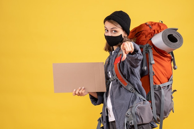 Reisendes mädchen mit schwarzer maske und rucksack mit pappe, die auf die kamera zeigt