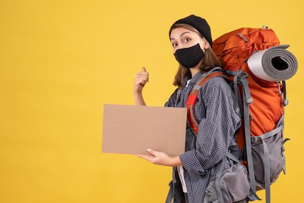Reisendes mädchen mit schwarzer maske und rucksack mit pappe, die auf gelb nach hinten zeigt