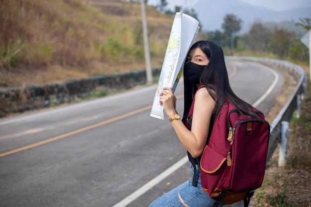 Reisendes mädchen sucht die richtige richtung auf der karte direction