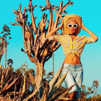 Reisendes modemädchen. kanarische insel. outfit im landhausstil. kaktus standort
