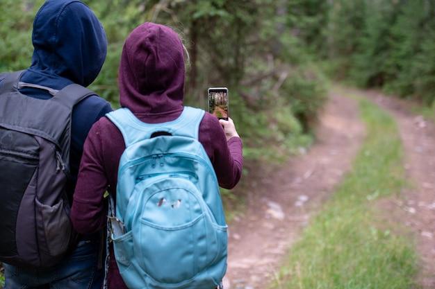 Reisendes paar, das foto der waldlandschaft mit smartphone nimmt