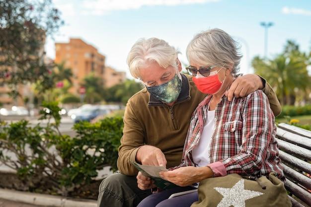 Reisendes paar konsultiert während der stadtrundfahrt eine karte, die aufgrund des coronavirus eine chirurgische maske trägt