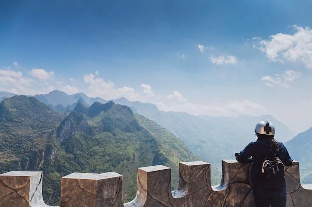 Reisendfrau, die auf die oberseite des berges am zwischenstopp für die besichtigung steht