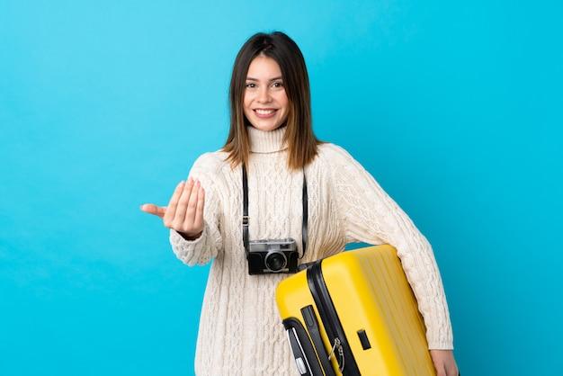 Reisendfrau, die einen gelben koffer über lokalisierter blauer wand hält