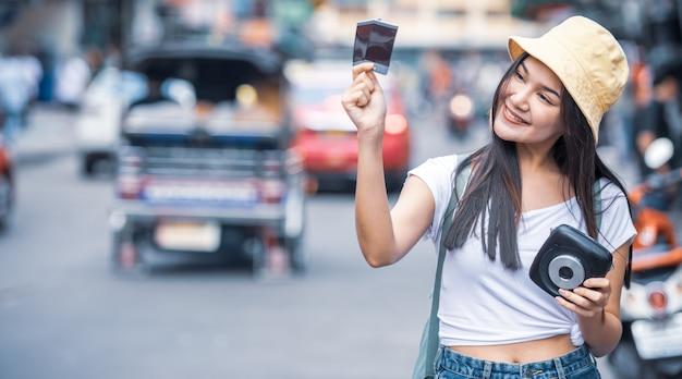 Reisendfrau, die sofortbildkamera und film an straße khao san, bangkok-stadt von thailand hält.