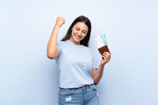 Reisendfrau mit bordkarte über der lokalisierten blauen wand, die einen sieg feiert