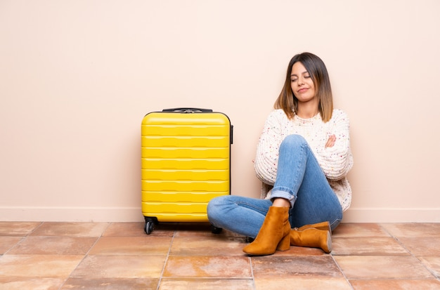 Reisendfrau mit dem koffer, der auf dem boden denkt eine idee sitzt