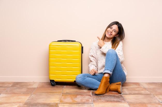 Reisendfrau mit dem koffer, der auf dem boden feiert einen sieg sitzt
