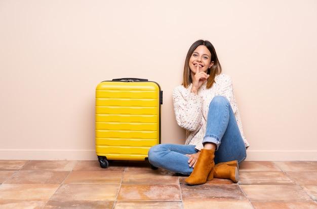 Reisendfrau mit dem koffer, der auf dem boden tut ruhegeste sitzt