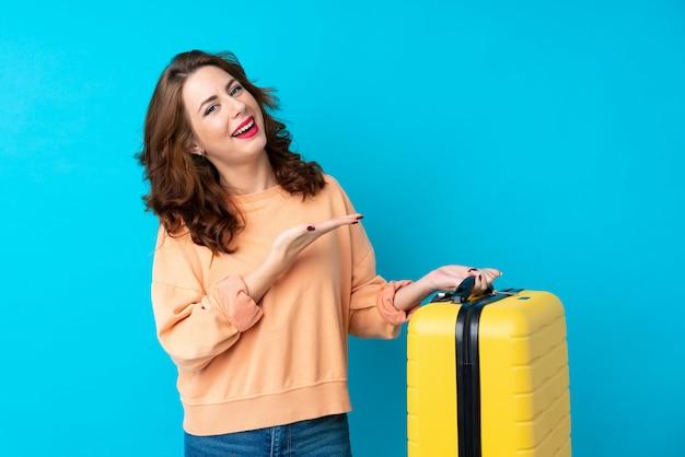 Reisendfrau mit dem koffer, der hände zur seite für die einladung ausdehnt zu kommen