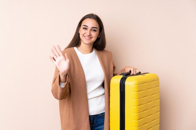Reisendfrau mit koffer begrüßend mit der hand mit glücklichem ausdruck