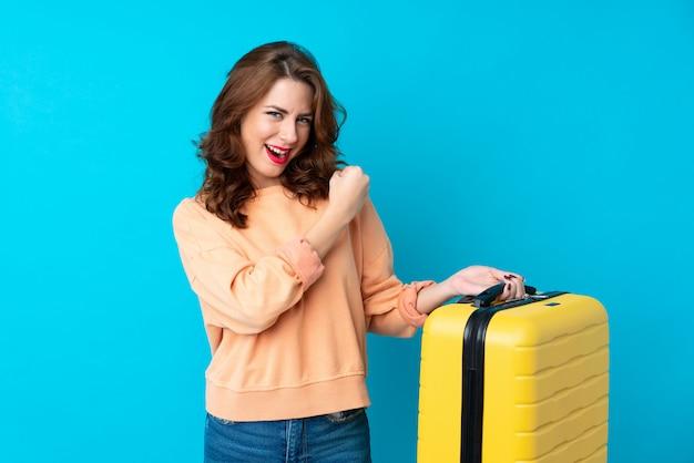 Reisendfrau mit koffer über dem lokalisierten blau, das einen sieg feiert