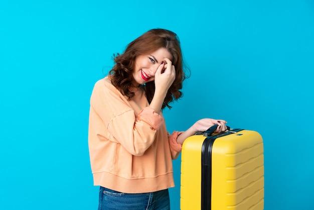 Reisendfrau mit koffer über lokalisiertem blauem lachen