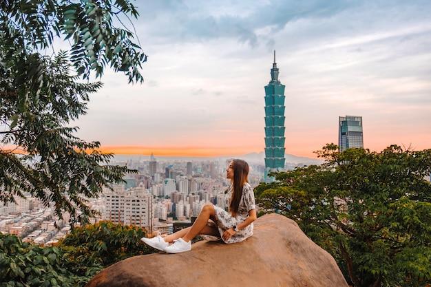 Reisendfrauen und -sonnenuntergang mit ansicht von skylinen von taipeh-stadtbild gebäude taipehs 101 der taipeh-finanzstadt, taiwan